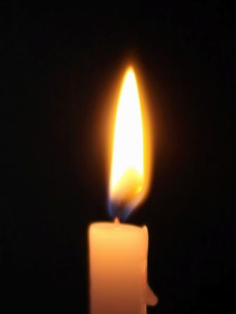 a candle shines in the darkness