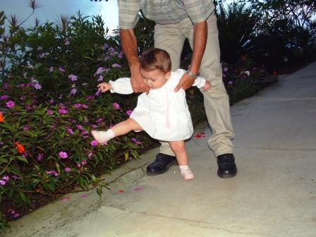a little girl takes big steps with the help of her grandfather