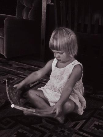 a little girl reads a book