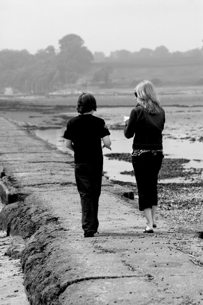 two people walk along a sea wall