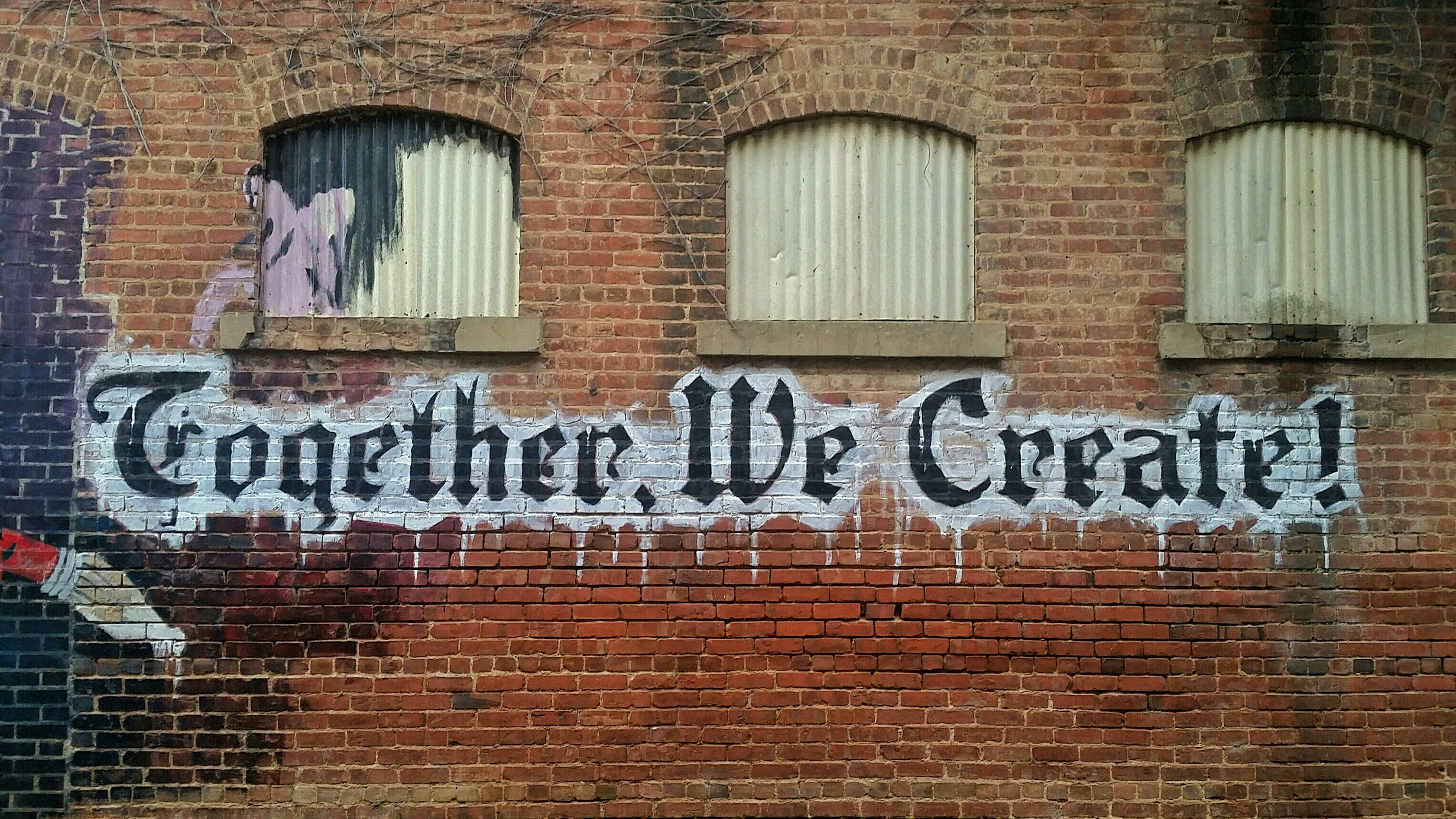 Together We Create! written on an old wall