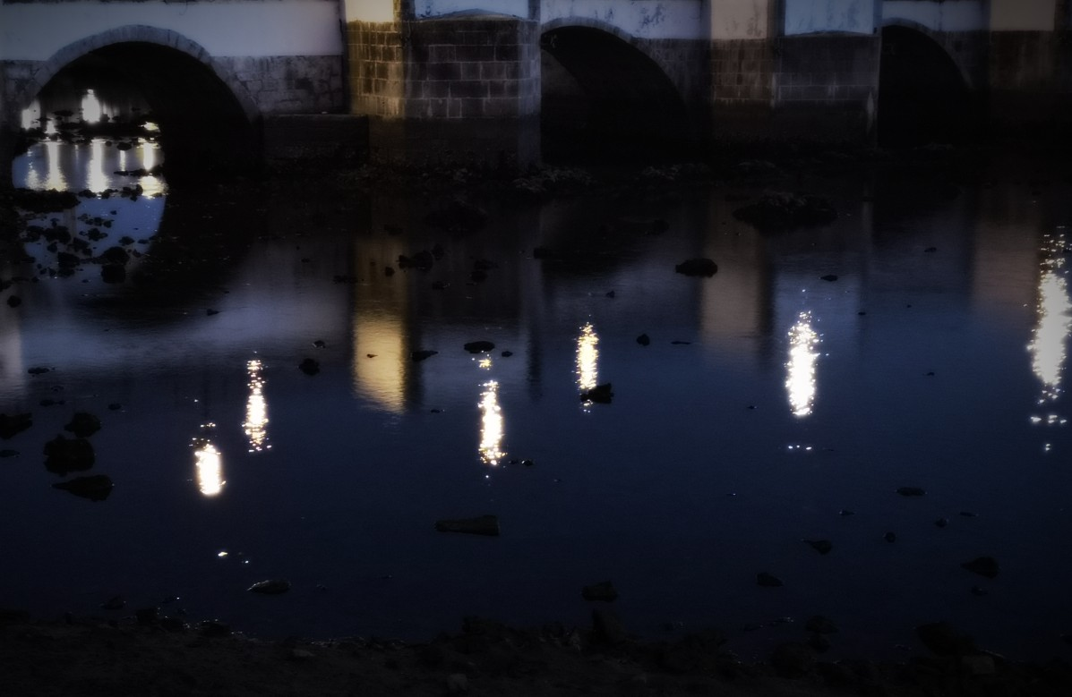 lights reflected in a night-time river below an old bridge.