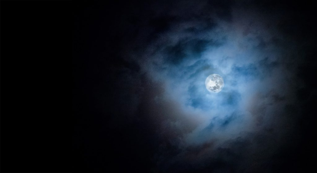 Alkmost full moon among clouds